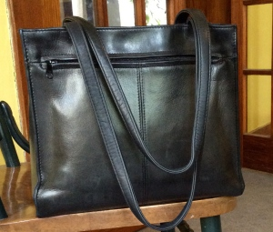 $2 leather handbag. I've carried this for three years now. It does a fit a good-sized book, which is an important feature.